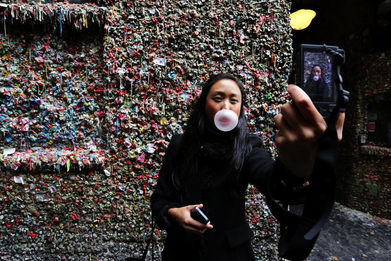 Silvia Lim CQ, visiting from Sweden, takes a self-portrait at the the Gum Wall attraction in Post Alley. It's her first visit having read about it in a tour guide. The covered brick walls are to be cleaned in a week. Tuesday Nov 3, 2015 Ref to on line gallery